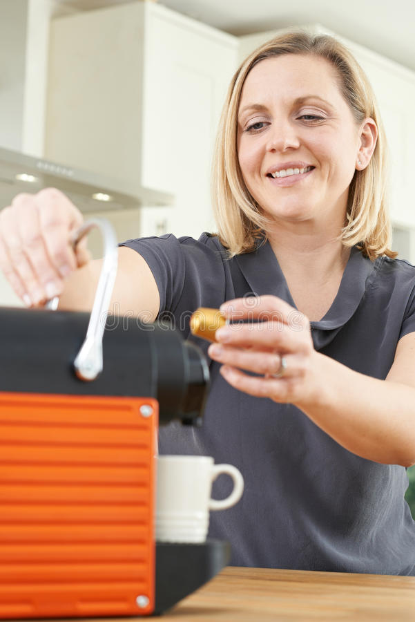Woman Using Coffee Capsule Machine In Kitchen stock photography