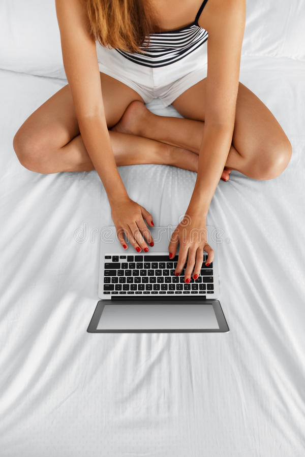 Woman Using Computer Home. Girl Working, Laptop Notebook On Bed. Woman Using Computer At Home. Closeup View Of Female Freelancer With Long Fit Legs Chatting royalty free stock image