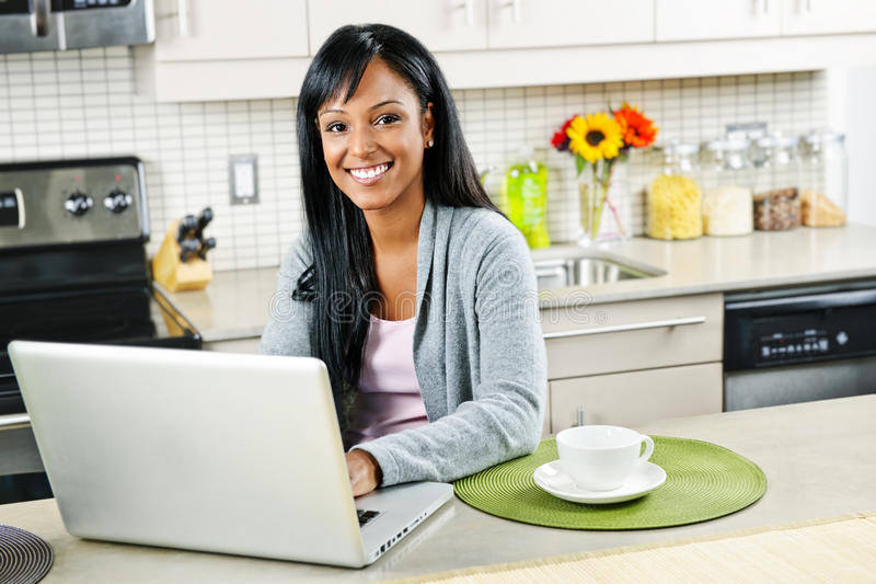 Download Woman Using Computer In Kitchen Stock Photo - Image: 21119750