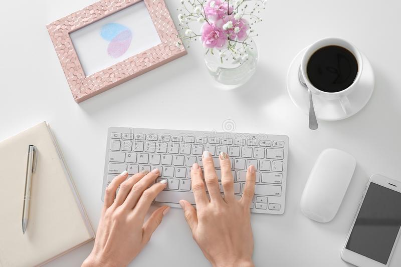 Woman using computer at white table, top view stock photos