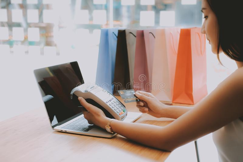 Woman using credit card swiping machine with shopping bags on table. payment with nfc technology. Woman using credit card swiping machine with shopping bags on royalty free stock photography