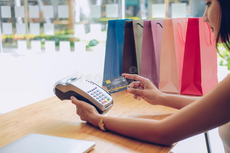 Woman using credit card swiping machine with shopping bags on table. payment with nfc technology. Woman using credit card swiping machine with shopping bags on stock photography