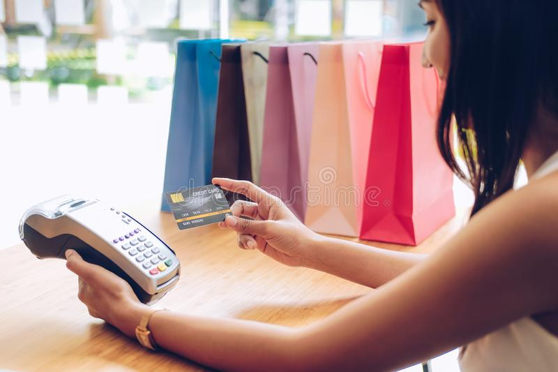 Woman using credit card swiping machine with shopping bags on table. payment with nfc technology. Woman using credit card swiping machine with shopping bags on stock image