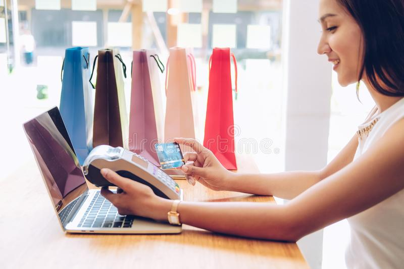 Woman using credit card swiping machine with shopping bags on table. payment with nfc technology. Woman using credit card swiping machine with shopping bags on royalty free stock photos
