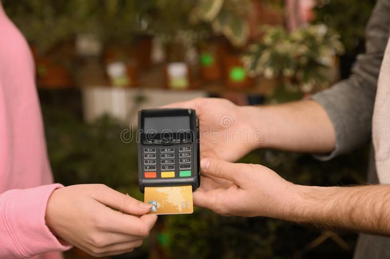 Woman using credit card for terminal payment in floral shop. Closeup stock photography