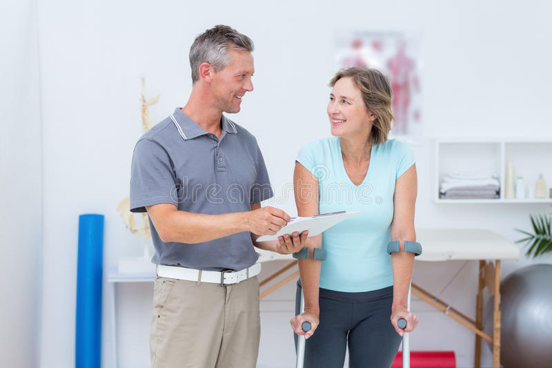 Woman using crutch and talking with her doctor royalty free stock photography