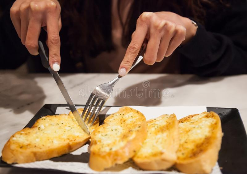 Woman using cutlery cut freshly Baked Tasty Homemade Garlic Bread servings. Food ingredient, bakery, pastry, snack, appetizer, royalty free stock photo