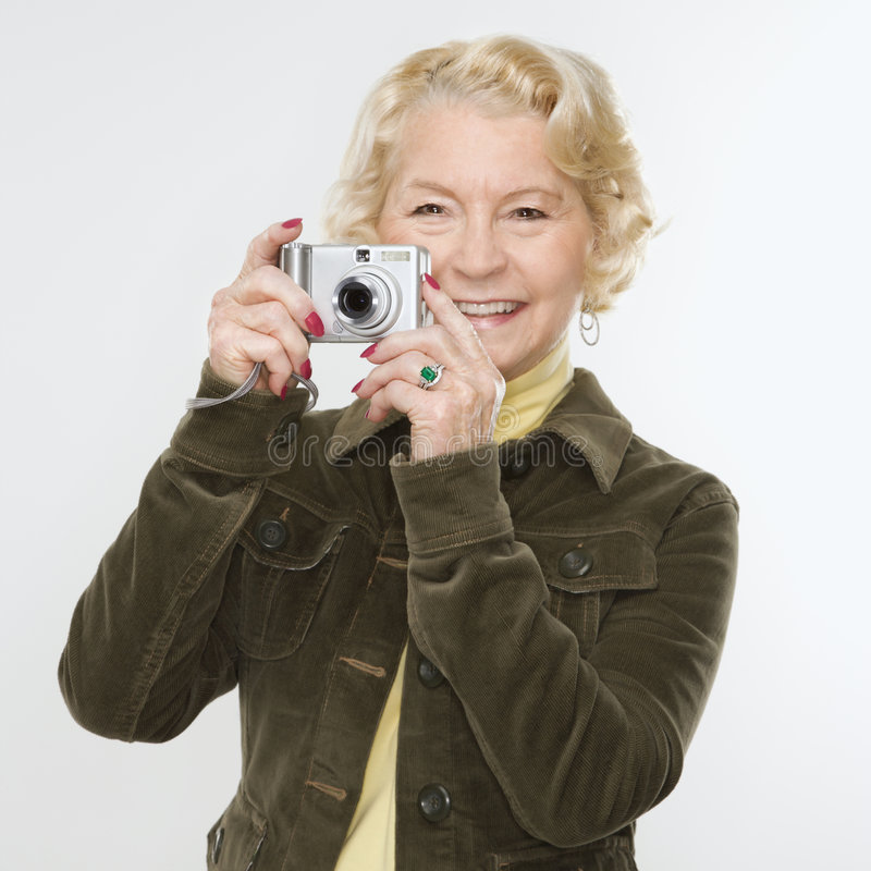 Woman using digital camera. Caucasian senior woman taking photo with digital camera of viewer royalty free stock photography