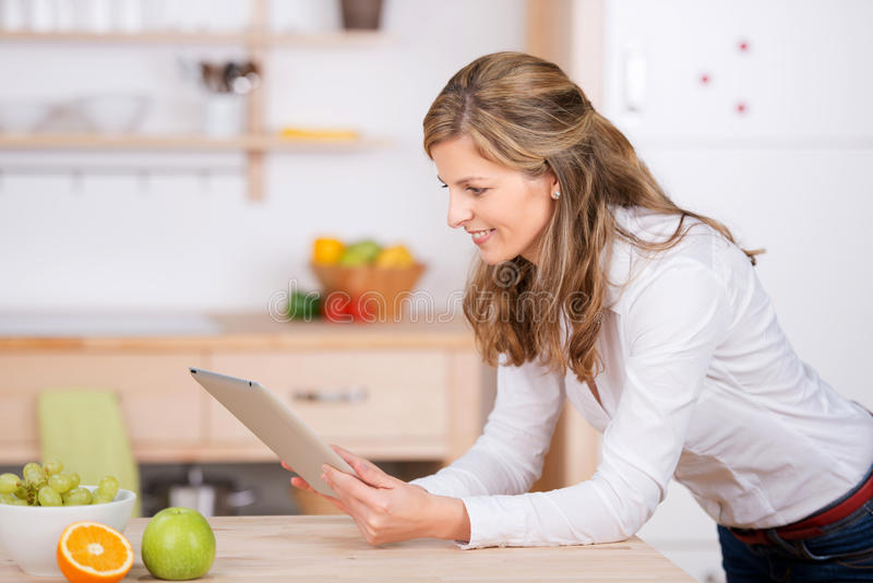 Woman using digital pad in the kitchen stock image