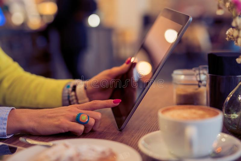 Woman using digital tablet in cafe royalty free stock photos