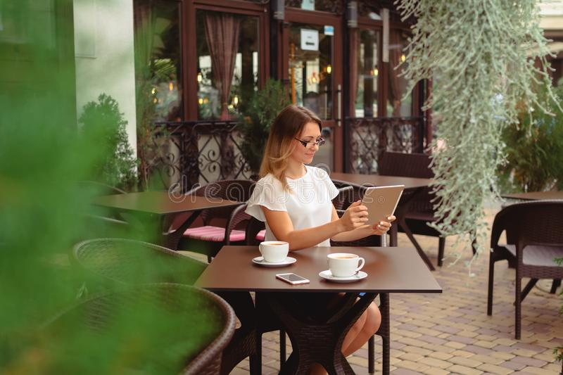 Woman using digital tablet and drinking coffee. Beautiful smiling caucasian business woman using digital tablet and drinking coffee in a cafe stock image