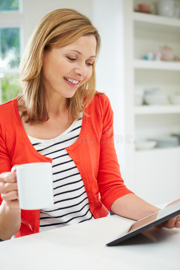 Woman Using Digital Tablet At Home In Kitchen