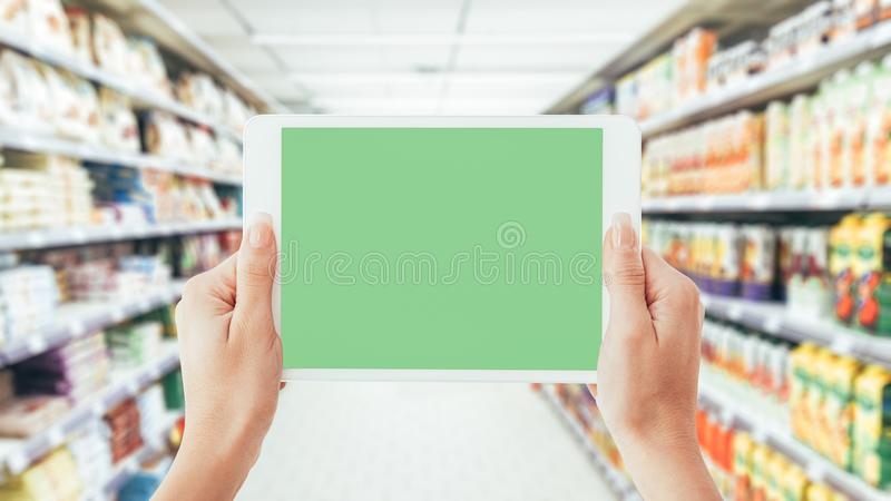 Woman using a tablet at the supermarket stock photos