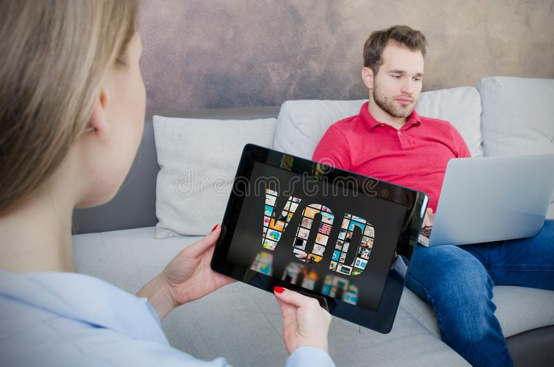 Woman using digital tablet for watching movie on VOD service stock photo