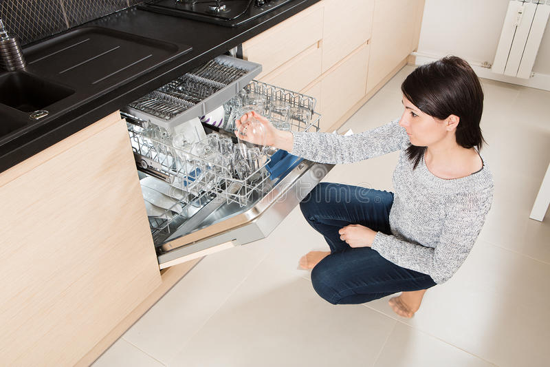 Woman using a dishwasher in a modern kitchen. stock photography