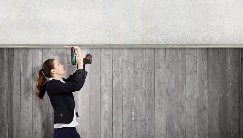 Woman using drill stock photos