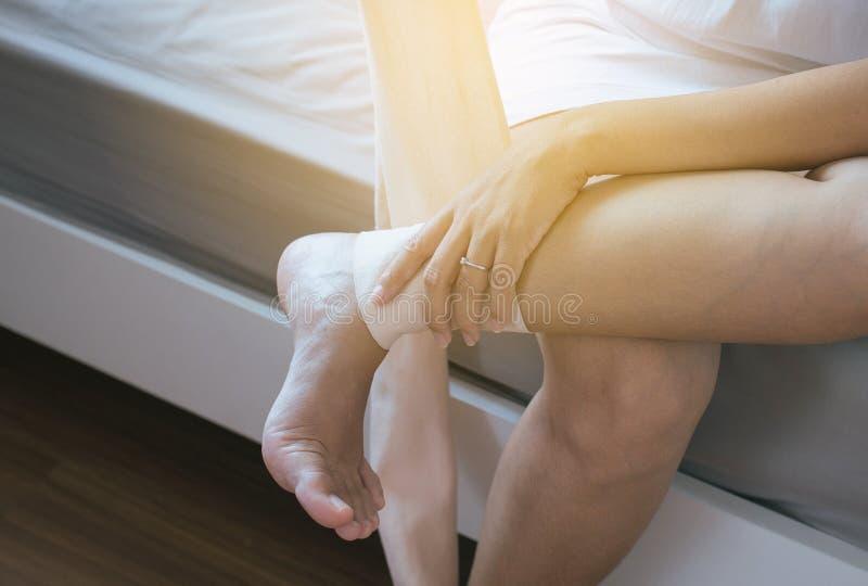 Woman using elastic bandage with legs,Female putting bandage on his injured knee stock photography