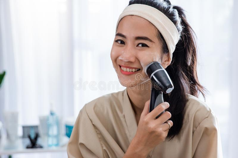 Woman using electric facial cleanser machine royalty free stock photography