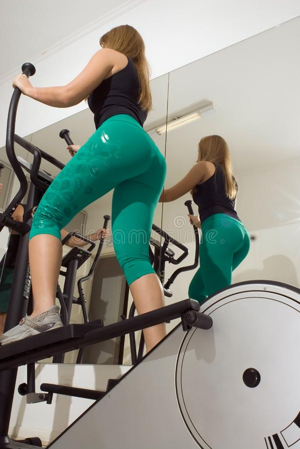 Woman Using Elliptical Machine royalty free stock image