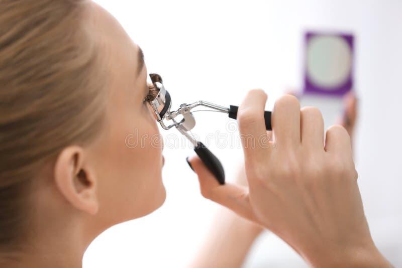 Woman using eyelash curler. Closeup stock photo