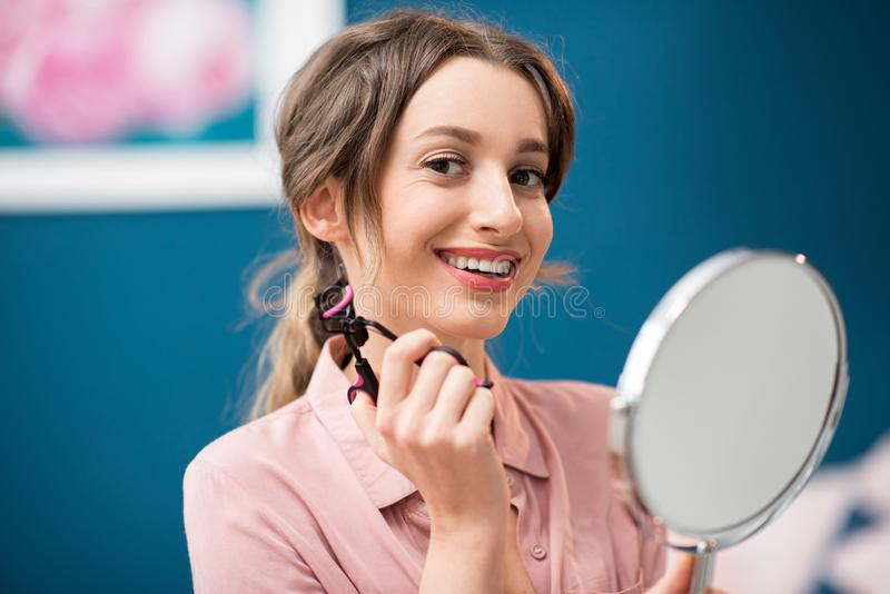 Woman using eyelash curler. Young woman using eyelash curler sitting with mirror on the blue wall background indoors stock photo