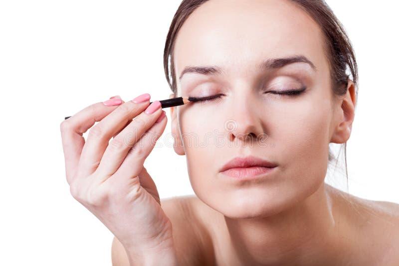 Woman using an eyeliner royalty free stock photos