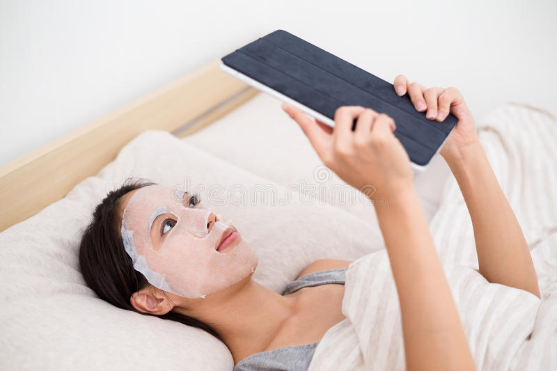 Woman using facial mask and tablet pc. On bed royalty free stock photos