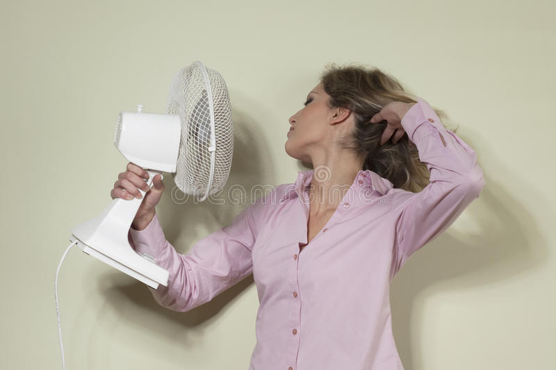 Woman using a fan. To cool off royalty free stock images