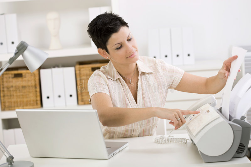 Woman using fax machine. At home office
