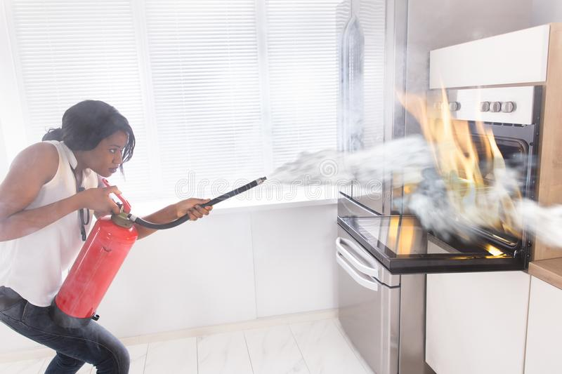 Woman Using Fire Extinguisher To Stop Fire Coming From Oven. Young African Woman Using Fire Extinguisher To Stop Fire Coming From Oven In Kitchen royalty free stock photography