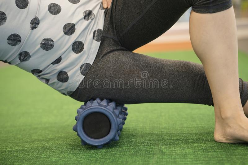 Woman using a foam roll on her leg to release tension stock photo