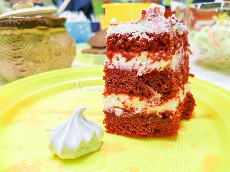 A woman using a fork to cut a piece of red velvet cake with cream and chocolate in white ceramic plate on wooden table.  stock photography