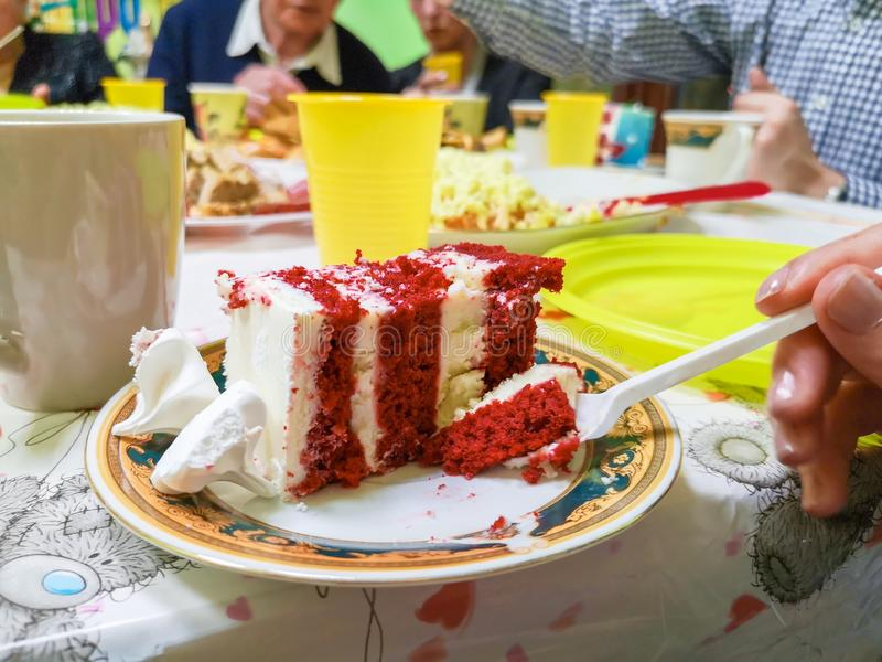 A woman using a fork to cut a piece of red velvet cake with cream and chocolate in white ceramic plate on wooden table royalty free stock images