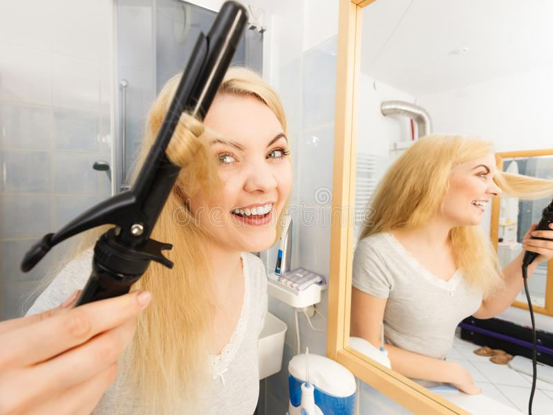 Woman using hair curler. Positive young woman preparing her blonde hair, using curling pin in home bathroom. Hairdo curler creating hairstyle royalty free stock photos