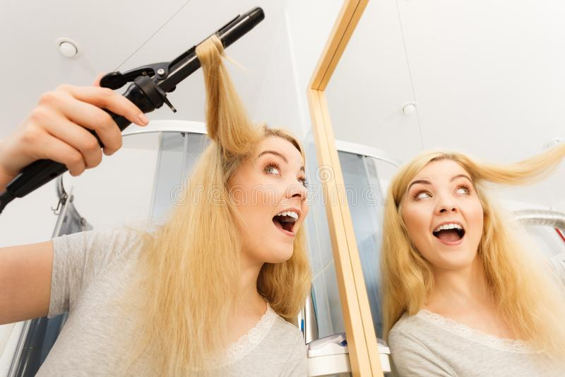 Woman using hair curler. Positive young woman preparing her blonde hair, using curling pin in home bathroom. Hairdo curler creating hairstyle stock photo