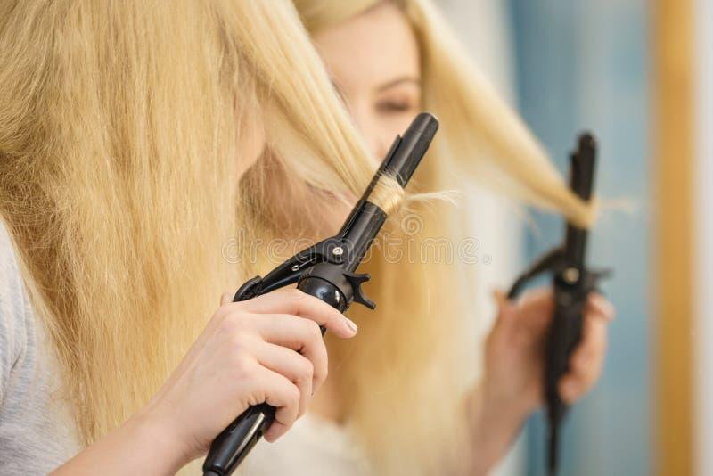 Woman using hair curler. Woman preparing her blonde hair, using curling pin in home bathroom. Hairdo curler creating hairstyle stock photo