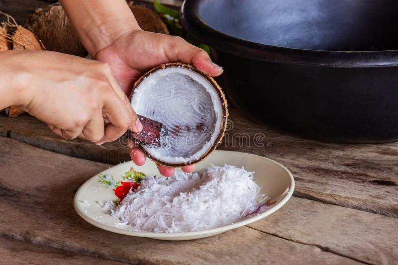 Woman using hand scraping coconut put the container for make dessert.and food. stock image