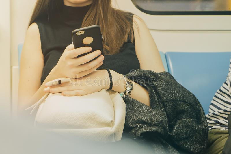 Woman using her cell phone in Subway stock photos