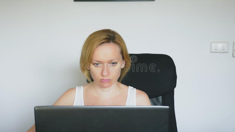A woman using her laptop, sitting at the table, angry and irritated, swears. Human emotions. internet addiction concept. A woman using her laptop, sitting at stock photography