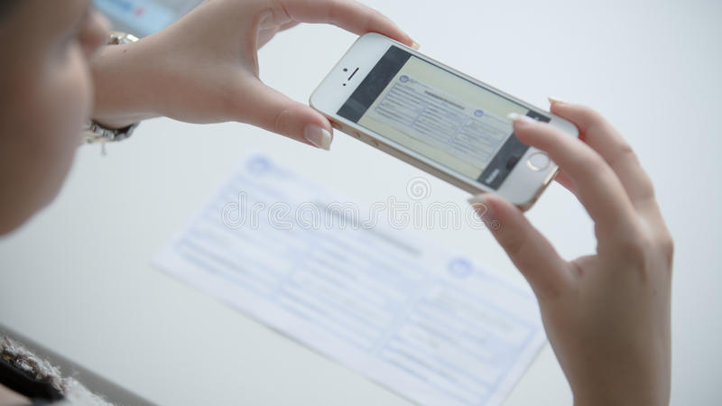 Woman using her phone to take picture of receipt or bill. Online paying bills from comfort of home.Online banking royalty free stock photography
