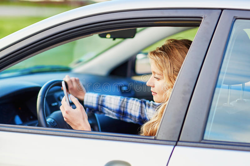 Woman using her smartphone while driving a car. Young woman using her smartphone while driving a car royalty free stock images