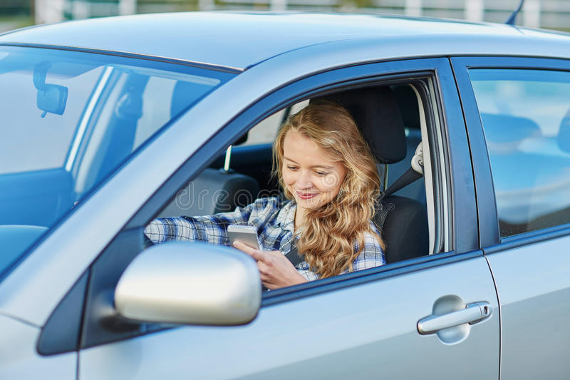 Woman using her smartphone while driving a car. Young woman using her smartphone while driving a car stock image