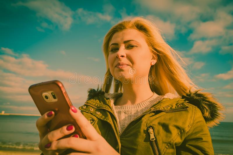 Woman using her smartphone outside, sunny day. Social media, technology, modern devices, internet concept. Woman teenager wearing warm coat using her smartphone royalty free stock photo