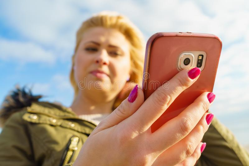 Woman using her smartphone outside, sunny day. Social media, technology, modern devices, internet concept. Woman teenager wearing warm coat using her smartphone royalty free stock photography