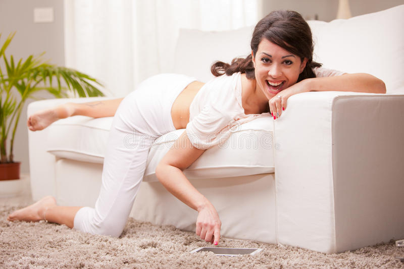 Woman using her tablet on the sofa. In her white living room royalty free stock photography