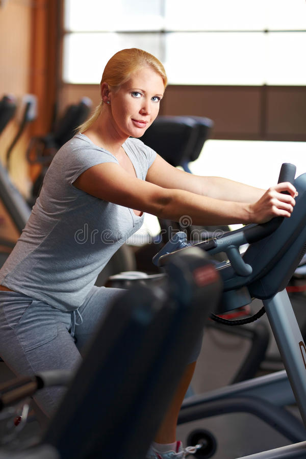 Woman using home trainer royalty free stock photography