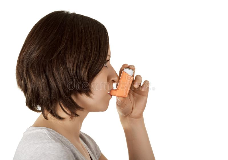Woman using inhaler and medication relieves asthma attack isolated on white. royalty free stock photos
