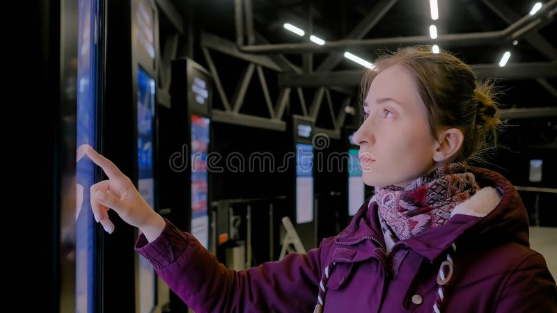 Woman using interactive touchscreen display of electronic multimedia kiosk. Portrait of woman using interactive touchscreen display of electronic multimedia royalty free stock images
