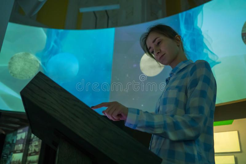 Woman using interactive touchscreen display at modern history museum. Portrait of woman using interactive touchscreen display of electronic multimedia kiosk at royalty free stock image