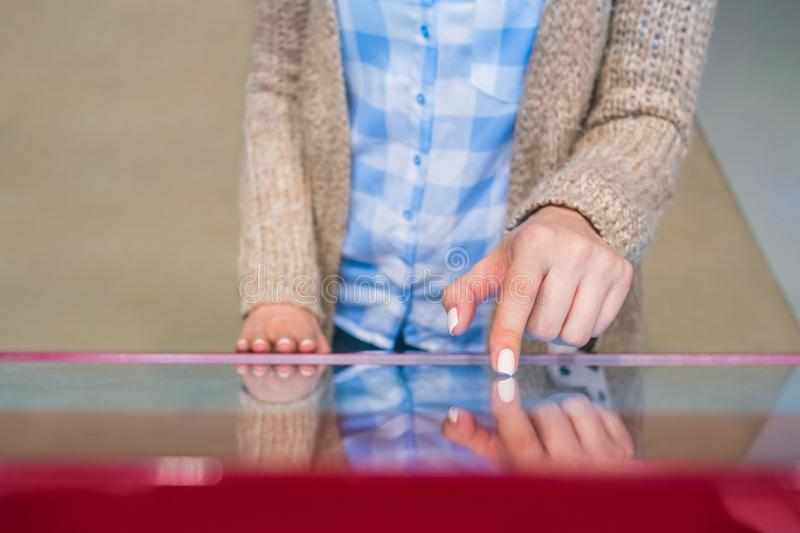 Woman using interactive touchscreen display at modern museum or exhibition. Woman hand using interactive touchscreen display of electronic multimedia terminal at stock photos
